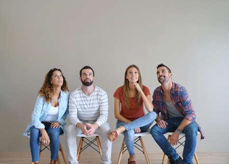 Jeunes adultes assis sur des chaises et regardant, isolé