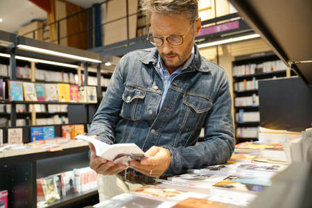 Man in bookstore looking at new books Zdjęcie Seryjne