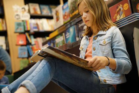 Young girl in book store reading comics Stock Photo - 86675663