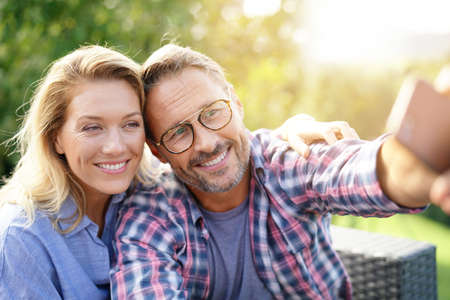 Portrait of cheerful mature couple taking selfie picture Stock fotó