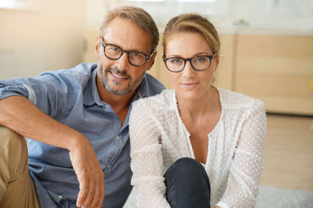 Mature couple with eyeglasses sitting on carpet at home