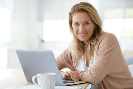 Attractive blond woman working on laptop computer at home