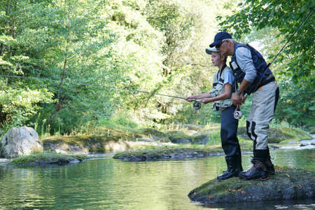 Dad with young boy fly-fishing in river Stock Photo - 86417252