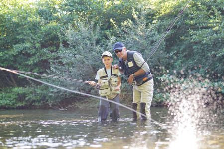 Father teaching son how to fly-fish in river