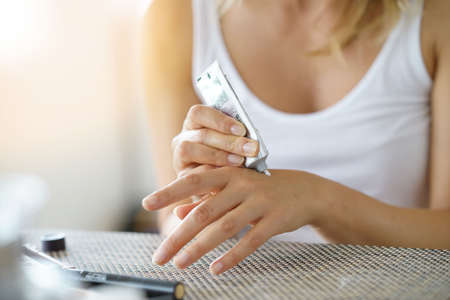 Closeup on woman's hands applying moisturizing hand-cream on