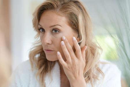 retrato de mujer rubia atractiva aplicar crema anti-envejecimiento