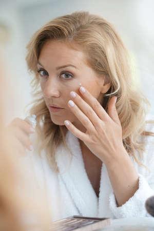 Portrait of attractive blond woman applying anti-aging cream