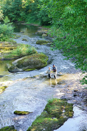 Aerial view of man with kid fly-fishing in river
