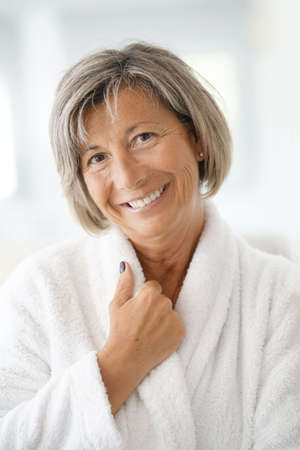 Portrait of smiling senior woman in bathrobe