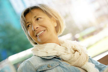 Portrait of smiling senior woman sitting on bench