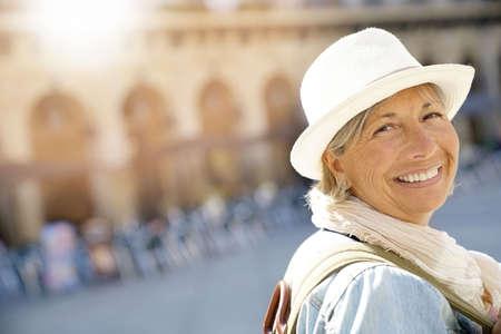 Senior vrouw met rugzak een Europese stad bezoeken