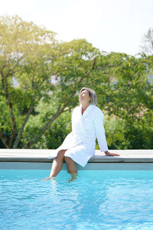 Senior woman with bathrobe relaxing by swimming-pool