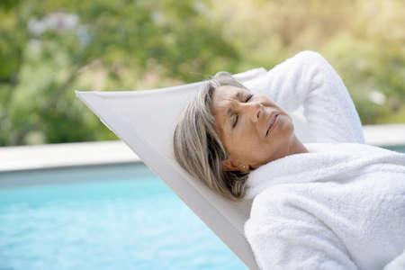 プールの長い椅子リラックスで年配の女性