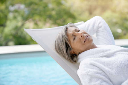 Senior woman in long chair relaxing by the pool