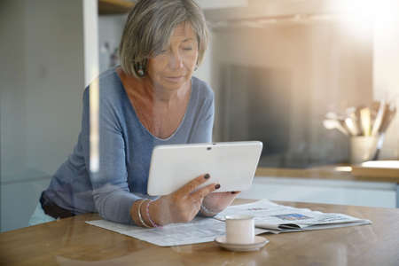 Mature woman at home reading news on digital tablet