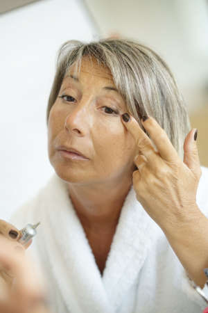 Senior woman in front of mirror applying eye concealer