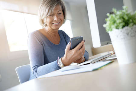 Senior woman working in office using smartphone