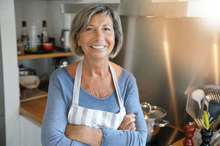 Cheerful Senior woman standing by stove in kitchen Lizenzfreie Bilder