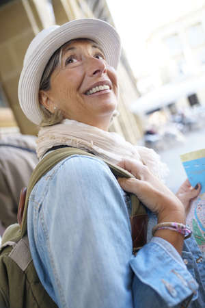 Senior woman traveling in european city, reading map Lizenzfreie Bilder