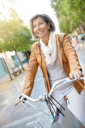 Senior woman riding city bike in town Lizenzfreie Bilder