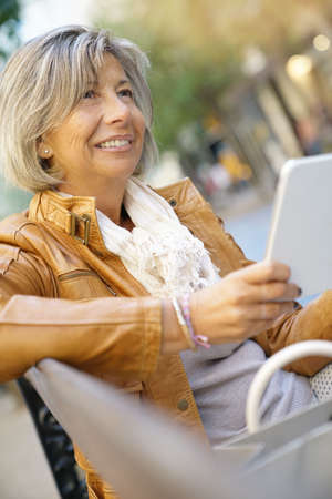 Senior woman in town using digital tablet