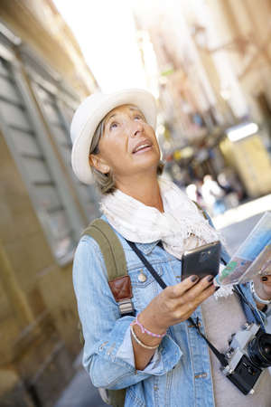 Senior woman visiting Spanish city, using smartphone and map