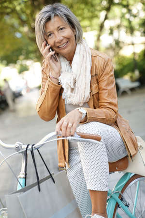 Senior woman in town with bike, talking on phone
