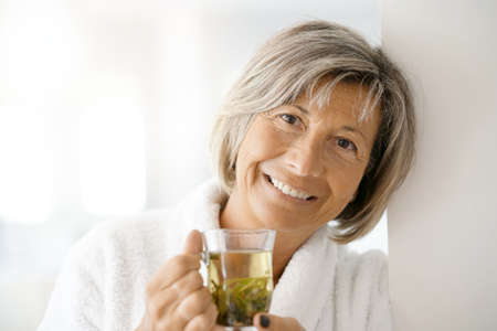 Senior woman in bathrobe drinking hot green tea Lizenzfreie Bilder