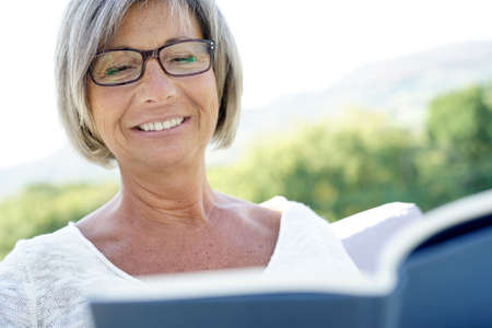 Senior woman with eyeglasses reading book in outdoor sofa