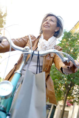 Portrait of senior woman riding city bike