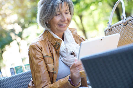 Senior woman at coffee shop terrace, using tablet Lizenzfreie Bilder