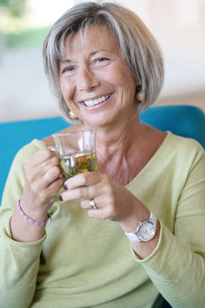 Senior woman relaxing in armchair drinking hot tea Lizenzfreie Bilder