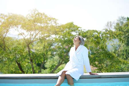 senior femme avec peignoir détente par la piscine