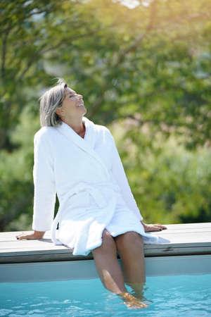 Femme âgée avec peignoir de détente au bord de la piscine