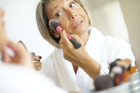 aging face: Senior woman in front of mirror putting makeup on Stock Photo