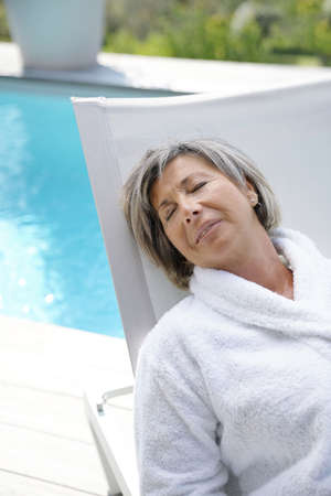 thalasso: Senior woman in long chair relaxing by the pool