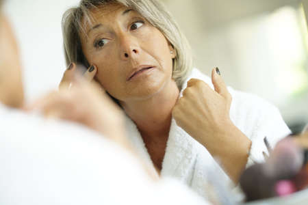 aging face: Senior woman in front of mirror looking at her skin and wrinkles