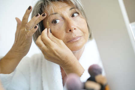 aging face: Senior woman removing eyebrows hair with tweezers