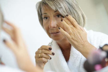 aging face: Senior woman in front of mirror applying eye concealer