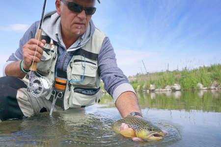モンタナ州の川でフライフィッシャーマンは茶色のマスをキャッチ 写真素材