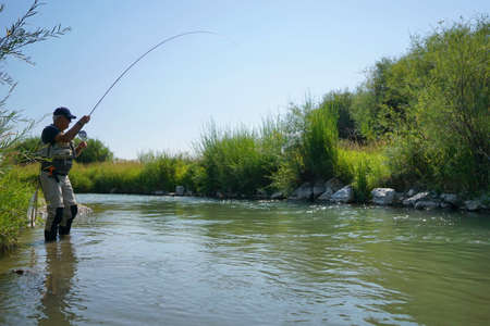 Fly fisherman fishing in river of Montana state Imagens