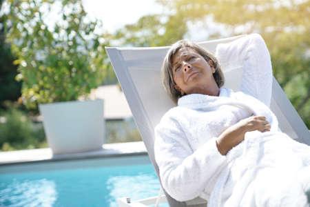 Femme âgée dans une chaise longue détente au bord de la piscine