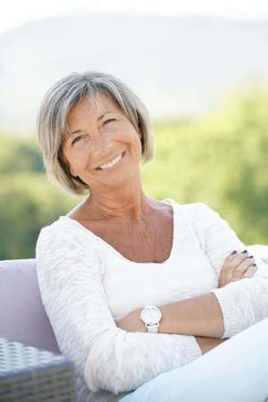 Portrait of cheerful senior woman relaxing in outdoors sofa Stock Photo