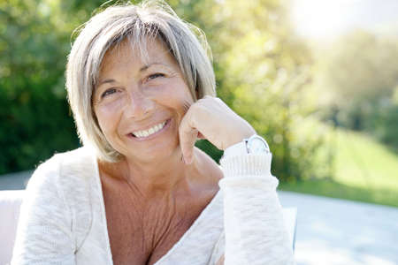 Portrait of cheerful senior woman relaxing in outdoors sofa Standard-Bild
