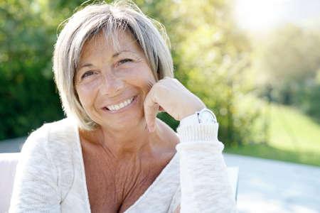 Portrait of cheerful senior woman relaxing in outdoors sofa Foto de archivo