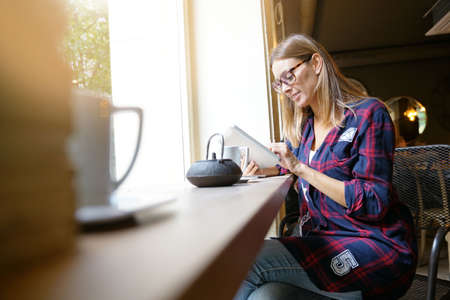 Trendy city girl in coffee shop connected with digital tablet