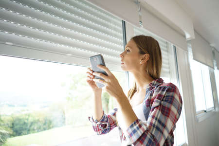 Woman using smartphone to control electric shutter