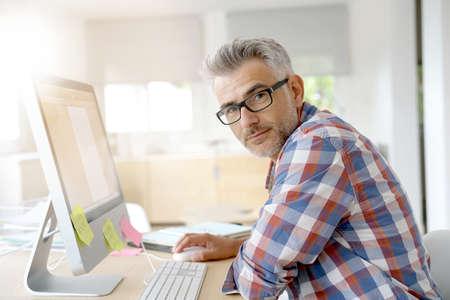 Web designer working in office on desktop computer Stock Photo