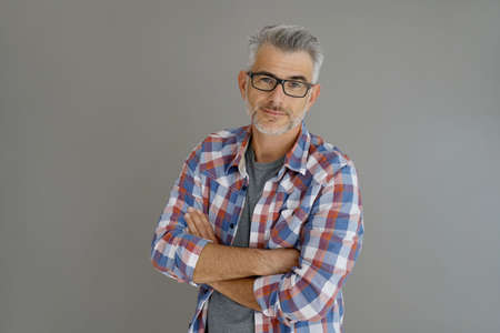 分離した背景の上に立って灰色の髪を持つカジュアルな男