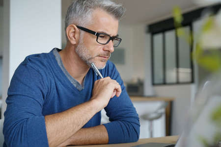 homeoffice: Middle-aged man working from home-office on laptop
